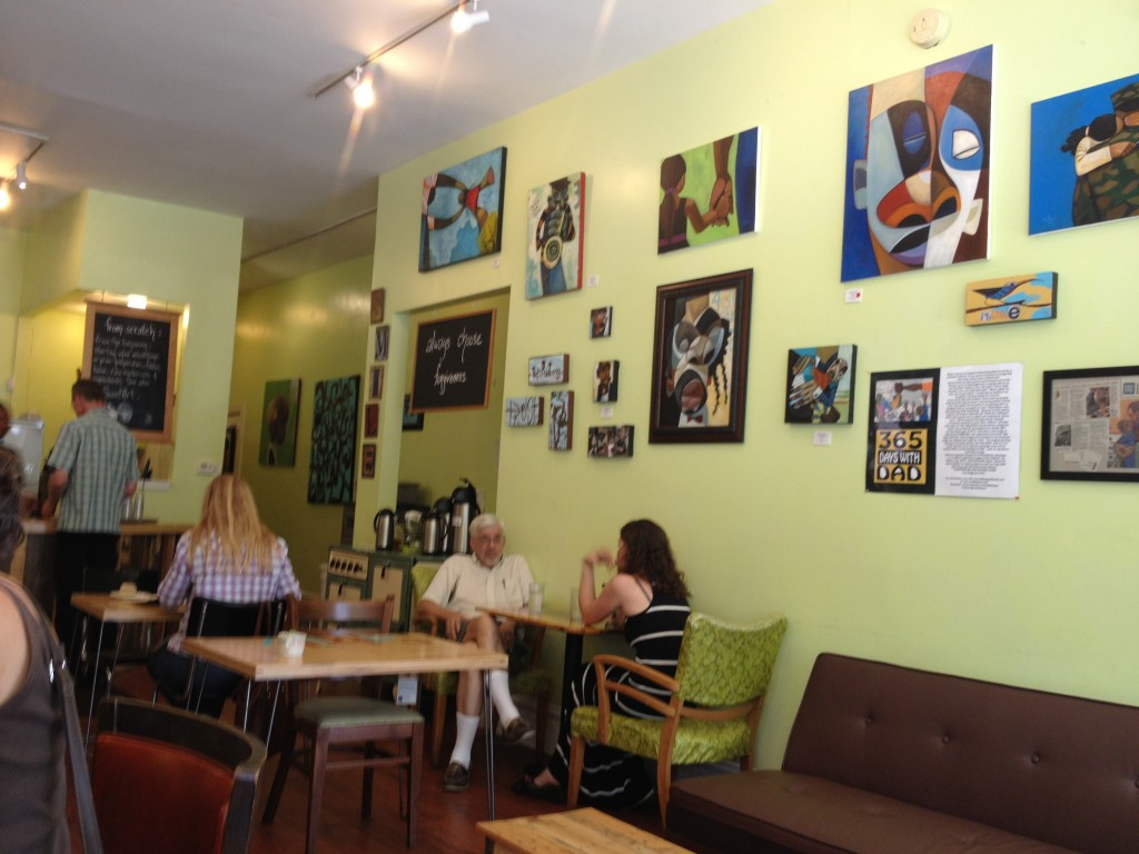 Paintings hung on one wall of cafe.